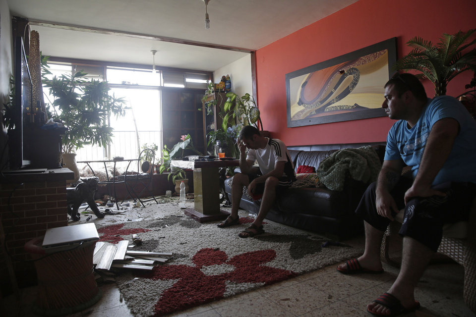 Photo - Israelis sit in their home that was hit by a rocket fired from the northern Gaza Strip Tuesday morning, in the costal city of Ashkelon, Israel, Tuesday, Aug. 26, 2014. (AP Photo/Tsafrir Abayov)