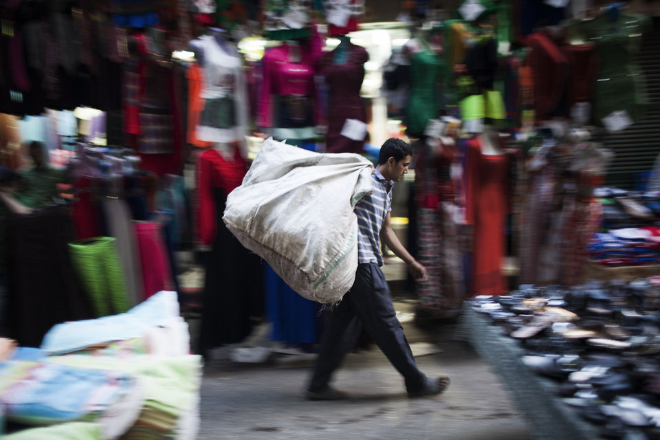 Photo - An Egyptian man carries garbage in the Ataba market on the eve of Eid al-Adha, or Festival of the Sacrifice, one of the most important celebrations in the Muslim calendar, in Cairo, Egypt, Monday, Oct. 14, 2013. (AP Photo/Manu Brabo)
