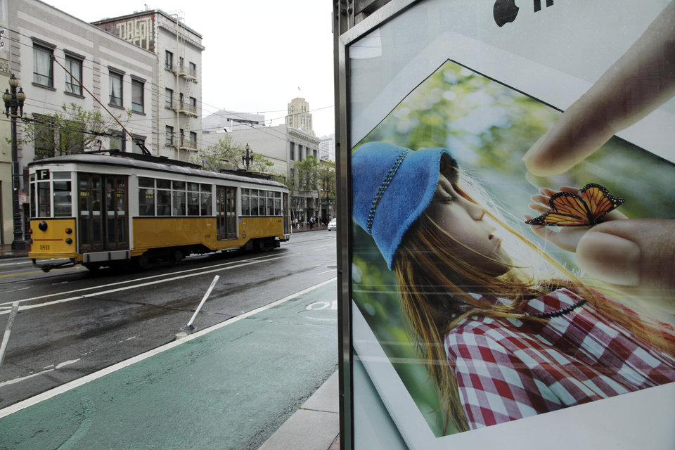 """Photo -   In this photo taken Thursday, May 3, 2012, an old streetcar passes a display for an Apple iPad near Twitter's new headquarters in San Francisco. With Twitter's new headquarters set to open there soon, residents of a San Francisco neighborhood notorious for crime, drugs and homelessness remain among the least likely to have any way to send a tweet, much less access to basic goods and services. At a recent weekend """"hackathon,"""" engineers and entrepreneurs sought ways to use tech to help people in the Tenderloin and Mid-Market Street area find food, housing, healthcare and jobs. In the process, city leaders hope to ease tensions between needy locals and newly arriving startups flush with cash. (AP Photo/Eric Risberg)"""