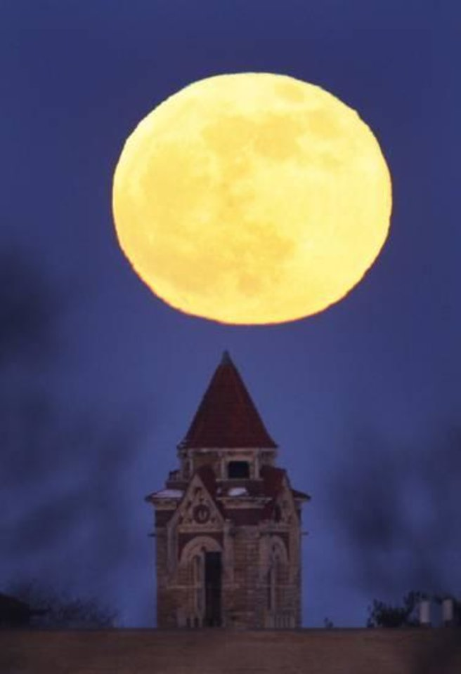 Photo - A blue moon rises above Dyche Hall at the University of Kansas Thursday, Dec. 31, 2009, in Lawrence, Kan. AP Photo