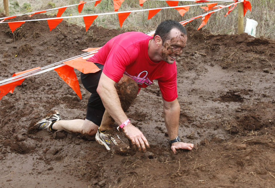 Nick Hamar comes out of a mud pit in the Juggernaut mud run at Edmond�s J.L. Mitch Park. The national mud run series is to raise money for Susan G. Komen for the Cure. PHOTOs BY PAUL HELLSTERN, THE OKLAHOMAN