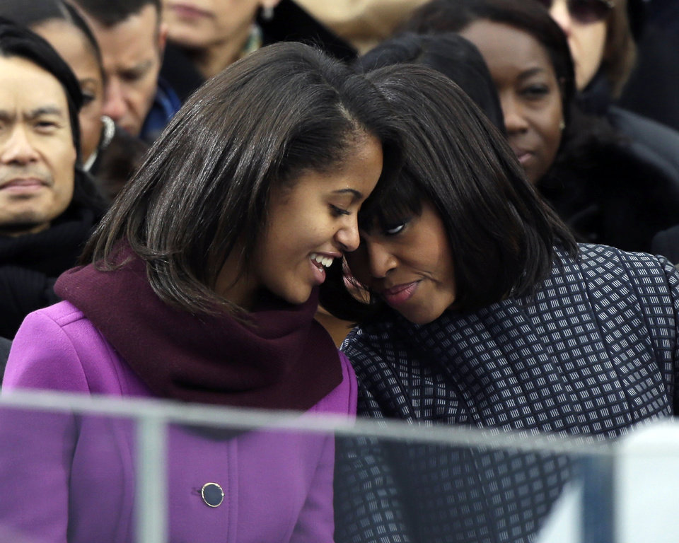 Photo - First lady Michelle Obama speaks with her daughter Malia at the ceremonial swearing-in for President Barack Obama at the U.S. Capitol during the 57th Presidential Inauguration in Washington, Monday, Jan. 21, 2013. (AP Photo/Pablo Martinez Monsivais)