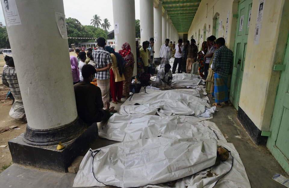 Photo - People cover their noses as they search through a line of dead bodies in hopes of identifying their relative at a school turned make-shift morgue for victims of the garment factory building collapse in Savar near Dhaka, Bangladesh, Friday, May 10, 2013. The death toll from a garment factory building that collapsed more than two weeks ago near the Bangladeshi capital soared past 1,000 on Friday, with no end in sight to the stream of bodies being pulled from the wreckage of the worst-ever garment industry disaster. (AP Photo/Ismail Ferdous)