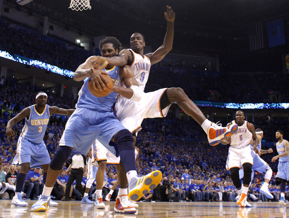Photo - Oklahoma City's Serge Ibaka (9) fights for the ball with Denver's Nene (31)during the first round NBA playoff game between the Oklahoma City Thunder and the Denver Nuggets on Sunday, April 17, 2011, in Oklahoma City, Okla. Photo by Chris Landsberger, The Oklahoman