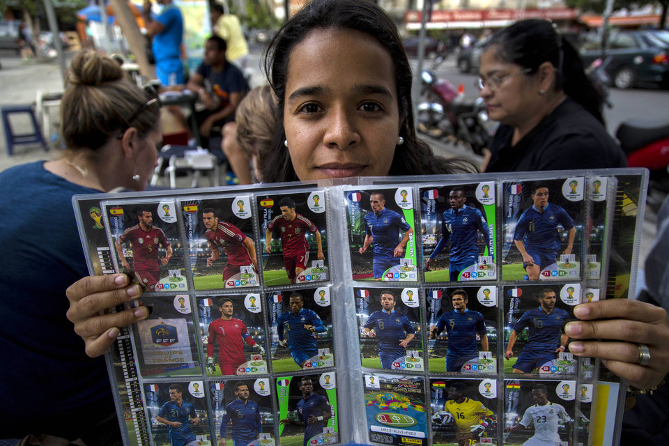 Photo - Hazel Petite shows a 2014 World Cup album edition at a meeting of collectors in Caracas, Venezuela, Saturday, June 21, 2014. Adults and children alike are spilling into plazas around the country to swap and buy business card-sized stickers with the faces of players and photos of Brazilian stadiums. Politicians, TV personalities, and professional collectors can all be found at ad-hoc trading centers, searching for the more than 600 stickers that constitute a complete 2014 collection. (AP Photo/Ramon Espinosa)
