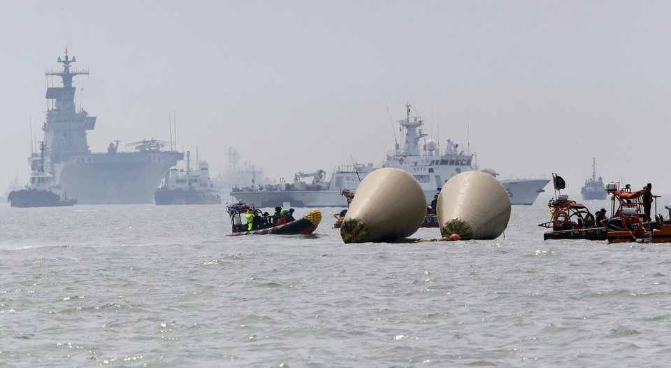 Photo - Searchers and divers look for people believed to have been trapped in the sunken ferry boat Sewol near the buoys which were installed to mark the vessel in the water off the southern coast near Jindo, south of Seoul, South Korea, Tuesday, April 22, 2014. One by one, coast guard officers carried the newly arrived bodies covered in white sheets from a boat to a tent on the dock of this island, the first step in identifying a sharply rising number of corpses from the South Korean ferry that sank nearly a week ago. (AP Photo/Lee Jin-man)