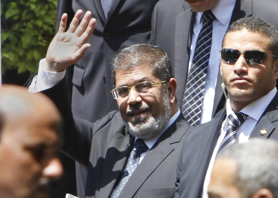 Photo -   Egyptian President Mohammed Morsi waves to photographers as he leaves the Arab League headquarters in Cairo, Egypt, Wednesday, Sept. 5, 2012. Morsi says Syrian leader Bashar Assad must learn from