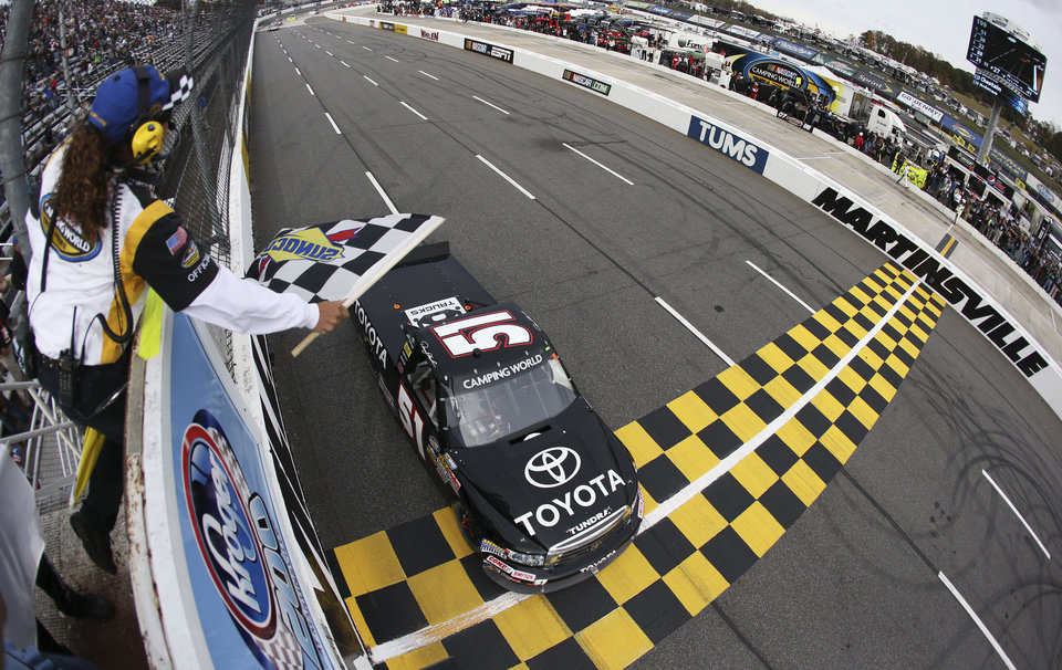 Photo -   Denny Hamlin (51) races past the checkered flag to win the NASCAR Camping World Truck Series Kroger 200 at Martinsville Speedway on Oct. 27, 2012 in Martinsville, Virginia. (AP Photo/Streeter Lecka/Getty Images/POOL)