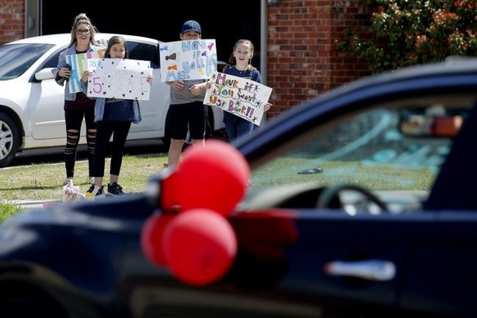 Photo -  Lacie Morgan, left, and her children, fifth-grader Paizley Morgan, 11, sixth-grader Sheckler Morgan, 12, and fourth-grader Journey Morgan hold signs as an Oakridge Elementary faculty caravan drives through their neighborhood around the Moore school, Tuesday, March 24, 2020. [Bryan Terry/The Oklahoman]