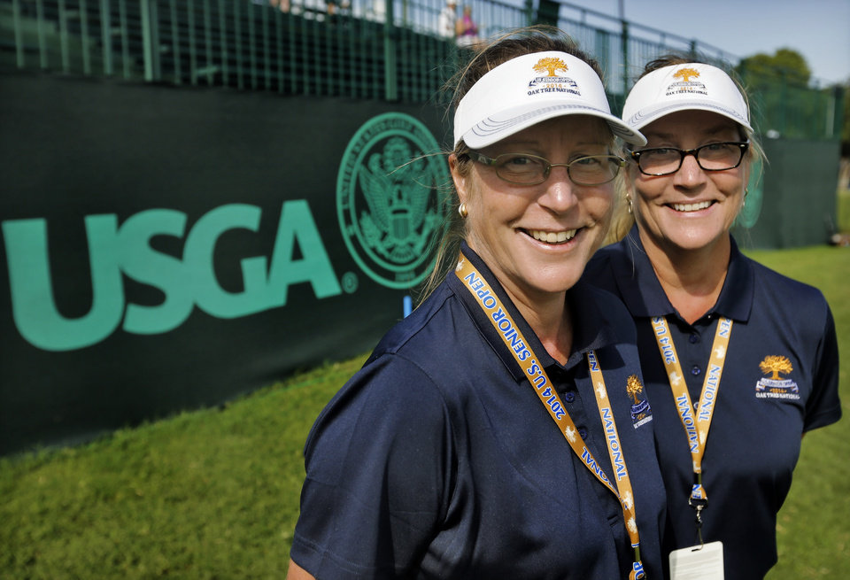 Photo - Twin sisters Mary Dominick and Marne Smith, from left, pose for a photo while serving as volunteers during the first round of the U.S. Senior Open Championship golf tournament at Oak Tree National in Edmond, Okla. on Thursday, July 10, 2014. Photo by Chris Landsberger, The Oklahoman