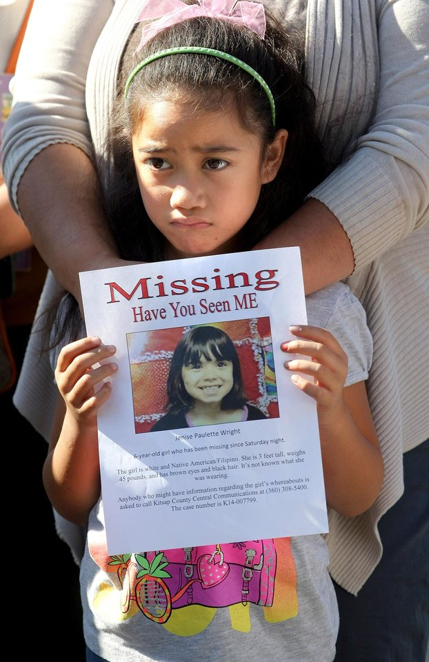 Photo - Moana Tuitasi,6, holds up a flyer of her missing classmate Jenise Wright at a law enforcement news conference on Tuesday, Aug. 5, 2014 in Bremerton, Wash. She came with her mom Ruby to show support for the search.  Jenise was last seen Saturday night at her home in the Steele Creek mobile home park. Her family reported her missing Sunday night. Wilson said the parents took an FBI lie-detector test and are cooperating. (AP Photo/Kitsap Sun, Larry Steagall)