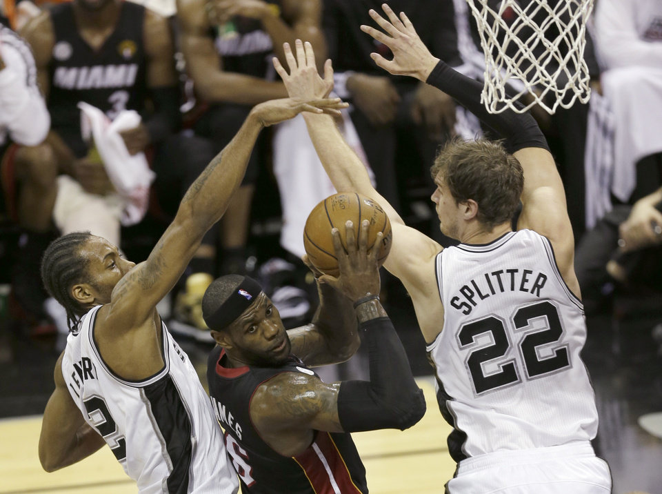 Photo - Miami Heat's LeBron James looks to pass between San Antonio Spurs' Kawhi Leonard (2) and San Antonio Spurs' Tiago Splitter (22), of Brazil, during the first half at Game 4 of the NBA Finals basketball series, Thursday, June 13, 2013, in San Antonio. (AP Photo/David J. Phillip)