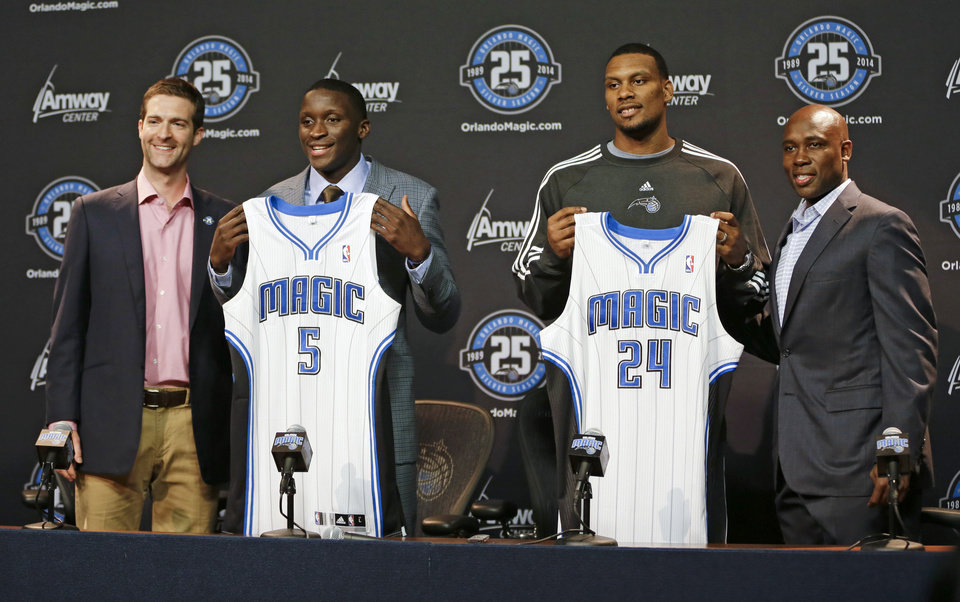 Orlando Magic NBA basketball draft picks Victor Oladipo (5) and Romero Osby (24), joined by Magic general manager Rob Hennigan, left, and coach Jacque Vaughn show off their new jerseys at a news conference, Friday, June 28, 2013, in Orlando, Fla. (AP Photo/John Raoux)