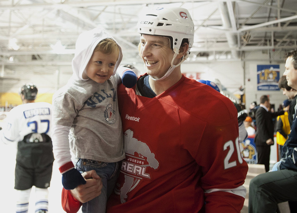 Photo -   Montreal Canadiens' Colby Armstrong chats with his son Cruise (2) at the end of the first period of a charity hockey game in Chateauguay, Quebec, Thursday, Sept. 27, 2012. The NHL canceled the rest of the preseason Thursday, just a day before negotiations were set to resume in an effort to end the lockout. (AP Photo/The Canadian Press, Graham Hughes)