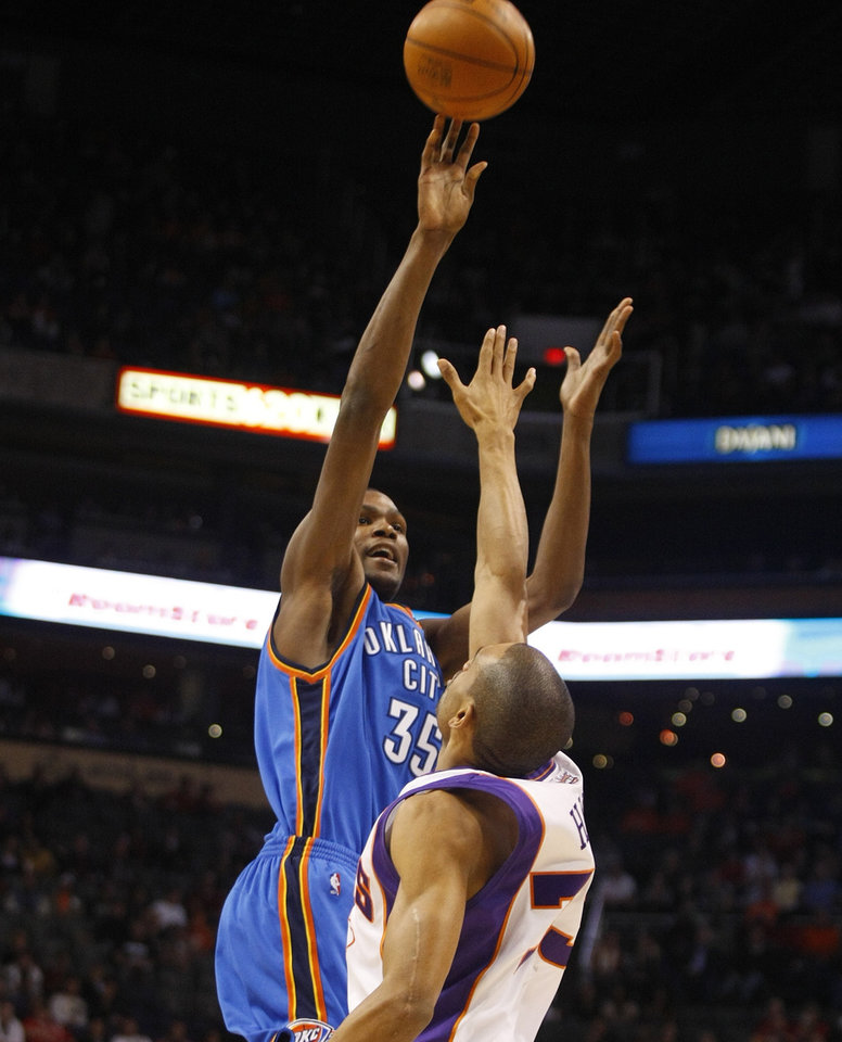 Photo - Oklahoma City Thunder's Kevin Durant, left, shoots over Phoenix Suns' Grant Hill during the first quarter of an NBA basketball game on Wednesday, Dec. 23, 2009, in Phoenix.  (AP Photo/Rick Scuteri)  ORG XMIT: AZRS103