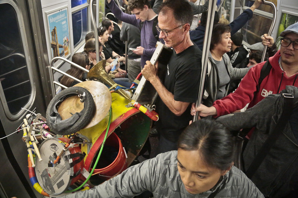 Photo - In this Wednesday, Oct. 9, 2013, photo, Jeffrey Masin, center, stands with his one-man band ensemble as he rides a subway train in New York.  Masin, from Waterford, Conn., has performed his one-man band show he calls