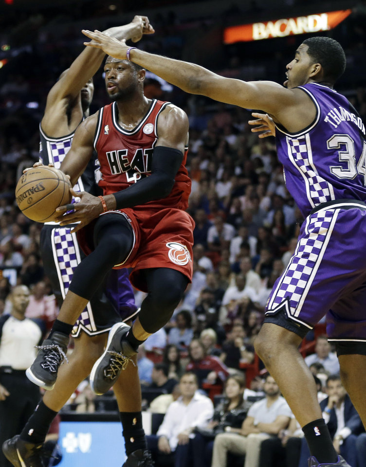Sacramento Kings' Jason Thompson (34) and DeMarcus Cousins (15) pressure Miami Heat's Dwyane Wade (3) to pass the ball during the first half of an NBA basketball game in Miami, Tuesday, Feb. 26, 2013. (AP Photo/J Pat Carter)
