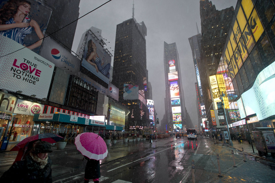 Photo - Pedestrians walk through Times Square as snow falls Friday, Feb. 8, 2013, in New York. A blizzard of potentially historic proportions threatens to strike the Northeast with 1 to 2 feet of snow forecast along the densely populated Interstate 95 corridor from New York City to Boston and beyond. (AP Photo/Frank Franklin II)