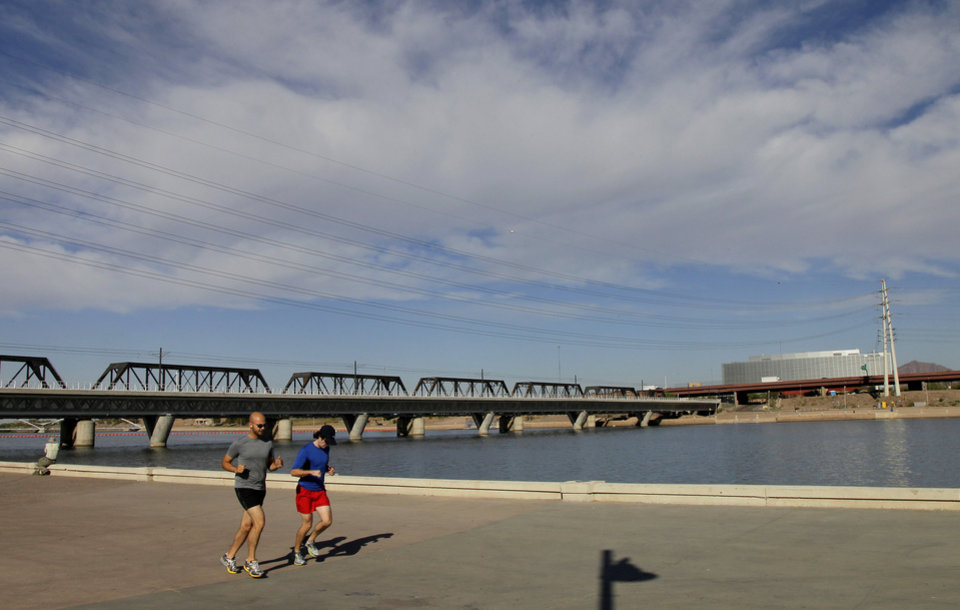A couple jogs along Tempe Town Lake, Monday, Nov. 26, 2012 in Tempe, Ariz. With cactus and strip malls obstructing the view at times, visitors could easily write Phoenix off as a place where water and culture are scarce. But this metropolis _ which includes upscale Scottsdale and college town Tempe _ is a nature lover's oasis with pristine peaks and vast Sonoran desert. (AP Photo/Matt York)