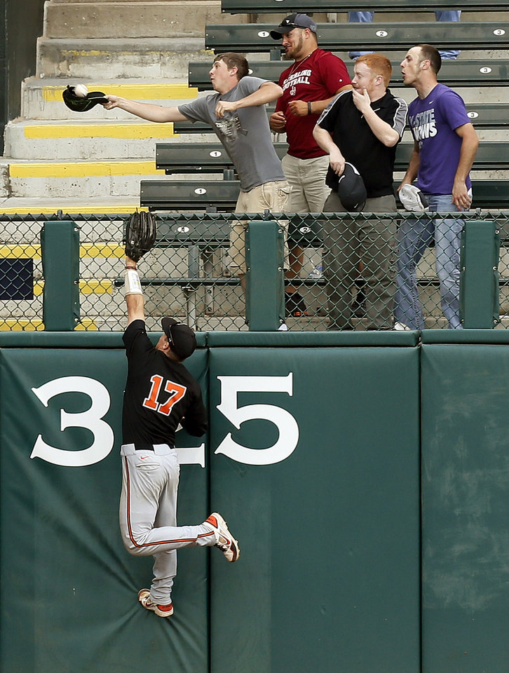 Photo - A fan uses his cap to catch a home-run ball by West Virginia's Brady Wilson (23) (not pictured) as Oklahoma State's Gage Green tries to to make the catch in the sixth inning during an NCAA baseball game between Oklahoma State and West Virginia in the Big 12 Baseball Championship tournament at the Chickasaw Bricktown Ballpark in Oklahoma City, Saturday, May 25, 2013. 