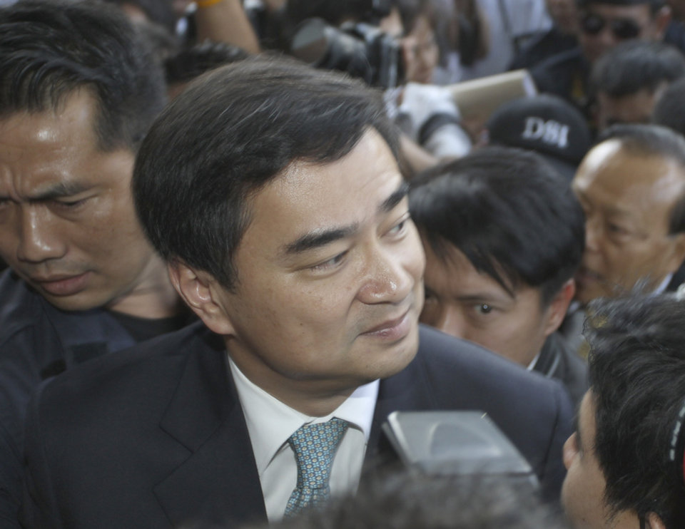 Former Thai Prime Minister Abhisit Vejjajiva arrives at the Department of Special Investigation (DSI) to acknowledge the murder charge Thursday, Dec. 13, 2012 in Bangkok, Thailand. Abhisit has met law enforcement officials to be formally charged with murder in connection with the violent suppression of anti-government protests in 2010. (AP Photo/Apichart Weerawong)