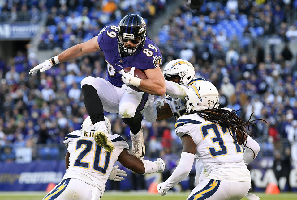 Photo - Baltimore Ravens tight end Mark Andrews (89) leaps over Los Angeles Chargers defenders as he rushes the ball in the second half of an NFL wild card playoff football game, Sunday, Jan. 6, 2019, in Baltimore. (AP Photo/Nick Wass)