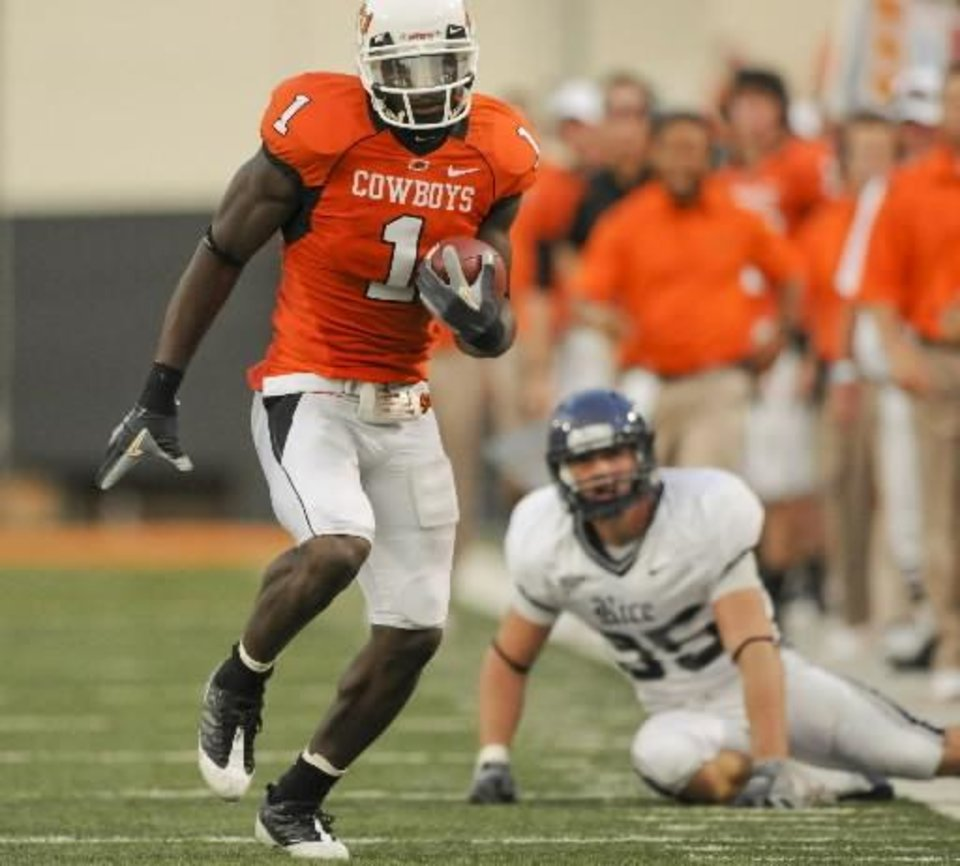 Photo - Rice safety Travis Bradshaw, right, watches as Oklahoma State wide receiver  Dez  Bryant, left, runs downfield during the first half of an NCAA college football game in Stillwater, Okla., Saturday, Sept. 19, 2009. Oklahoma State defeated Rice 41-24. (AP Photo/Brody Schmidt)