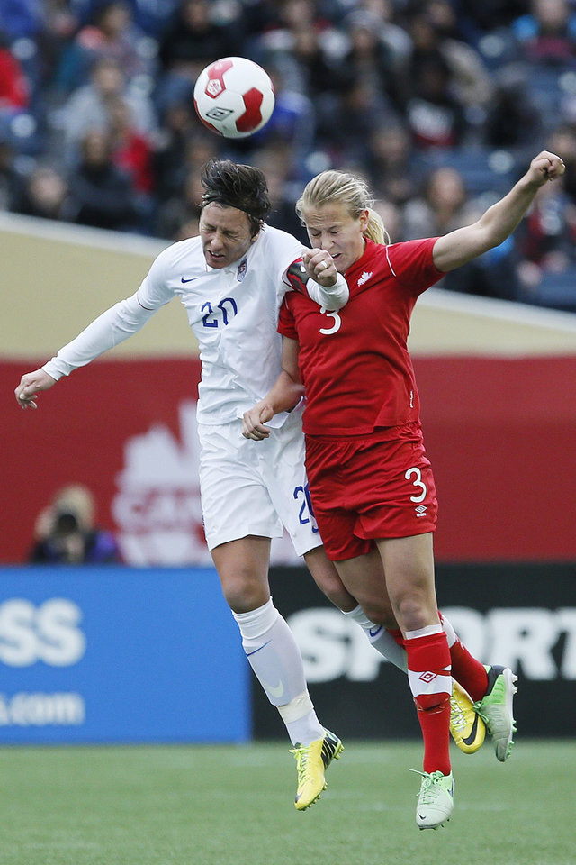 Photo - United States' forward Abby Wambach (20) goes up for the header against Canada's defender Rebecca Quinn (3) during first half of an exhibition soccer match in Winnipeg, Manitoba, Thursday, May 8, 2014. (AP Photo/The Canadian Press, John Woods)