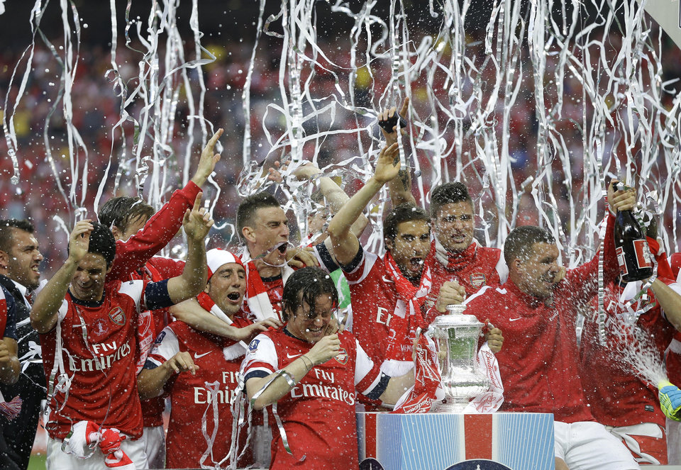 Photo - Arsenal players celebrate after winning the English FA Cup final soccer match between Arsenal and Hull City at Wembley Stadium in London, Saturday, May 17, 2014. Arsenal won 3-2 after extra-time. (AP Photo/Kirsty Wigglesworth)