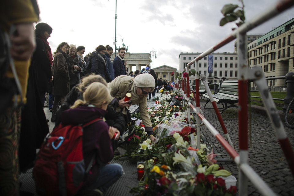 Photo - People lay down flowers to mourn for the victims killed in the Friday's attacks in Paris, France, in front of the French Embassy near the Brandenburg Gate in Berlin, Saturday, Nov. 14, 2015.  French President Francois Hollande said more than 120 people died Friday night in shootings at Paris cafes, suicide bombings near France's national stadium and a hostage-taking slaughter inside a concert hall. (AP Photo/Markus Schreiber)