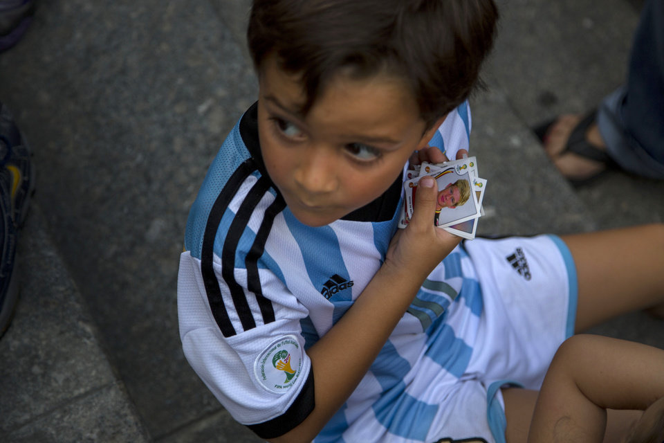 Photo - A child wearing the team jersey of Argentina holds photos of soccer players he needs to get, to complete his World Cup sticker album, at a meeting of collectors in Caracas, Venezuela, Saturday, June 21, 2014.  While soccer has long taken a backseat to baseball and even basketball in Venezuela, the ritual of sicker collection still sparks a frenzy. Politicians, TV personalities, and professional collectors can all be found at ad-hoc trading centers, searching for the more than 600 stickers that constitute a complete 2014 collection. (AP Photo/Ramon Espinosa)