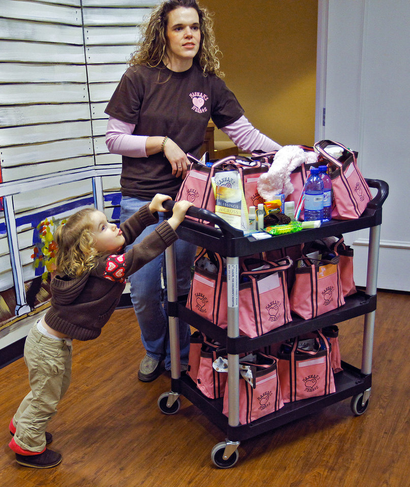 Photo - Hannah Linsky, 3, helps her mother Deonna prepare a cart of Hannah's Hearts bags to deliver to families in the neonatal intensive care unit at OU Medical Center's Children's Hospital.  CHRIS LANDSBERGER - CHRIS LANDSBERGER