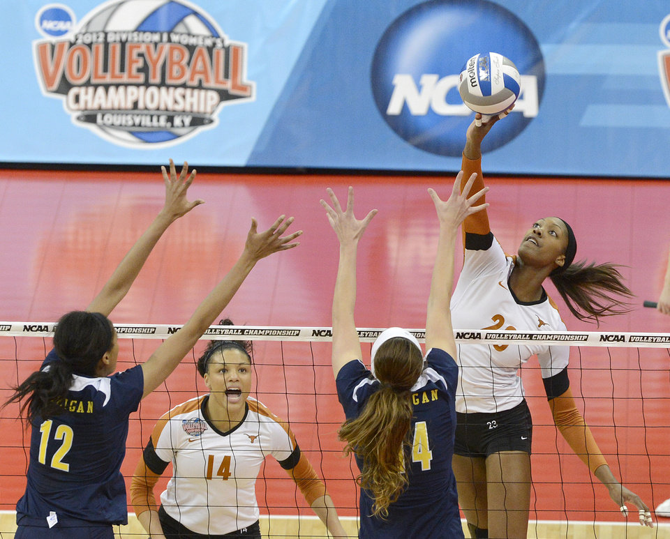 Texas outside hitter Bailey Webster, right, attempts to spike the ball past the defense of Michigan's Krystalyn Goode, left, and Claire McElheny during the national semifinals of the NCAA college women's volleyball tournament Thursday, Dec. 13, 2012 in Louisville, Ky. (AP Photo/Timothy D. Easley)