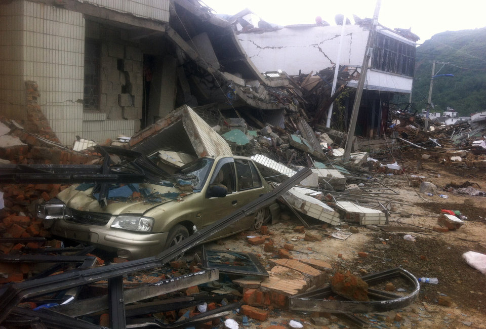 Photo - A car is crushed by a collapsed building in the epicenter of an earthquake that struck the town of Longtoushan in Ludian county in southwest China's Yunnan province Monday, Aug. 4, 2014. Rescuers dug through shattered homes Monday looking for survivors of a strong earthquake in southern China's Yunnan province that toppled thousands of homes on Sunday, killing hundreds and injuring more than a thousand people (AP Photo) CHINA OUT