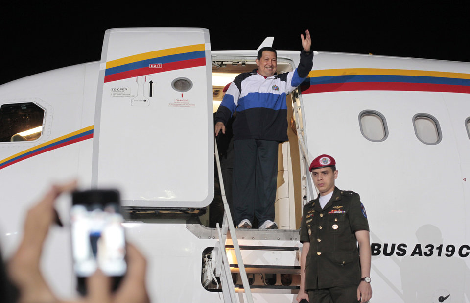 Photo -   In this photo provided by Miraflores Presidential Press Office, Venezuela's President Hugo Chavez waves from his plane upon arrival to the airport in Barinas, Venezuela, Wednesday April 4, 2012. Chavez returned to Venezuela on Wednesday night after his latest round of radiation therapy treatment in Cuba. (AP Photo/Miraflores Presidential Office)