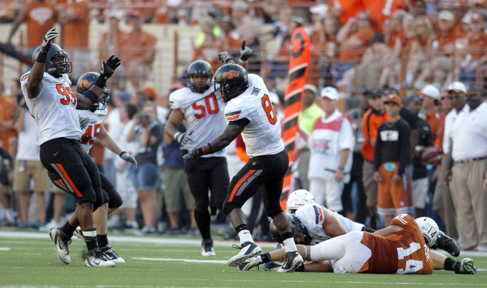 The OSU defense celebrates a fumble recovery as Texas\' David Ash (14) lies on the ground during second half of a college football game between the Oklahoma State University Cowboys (OSU) and the University of Texas Longhorns (UT) at Darrell K Royal-Texas Memorial Stadium in Austin, Texas, Saturday, Oct. 15, 2011. Photo by Sarah Phipps, The Oklahoman