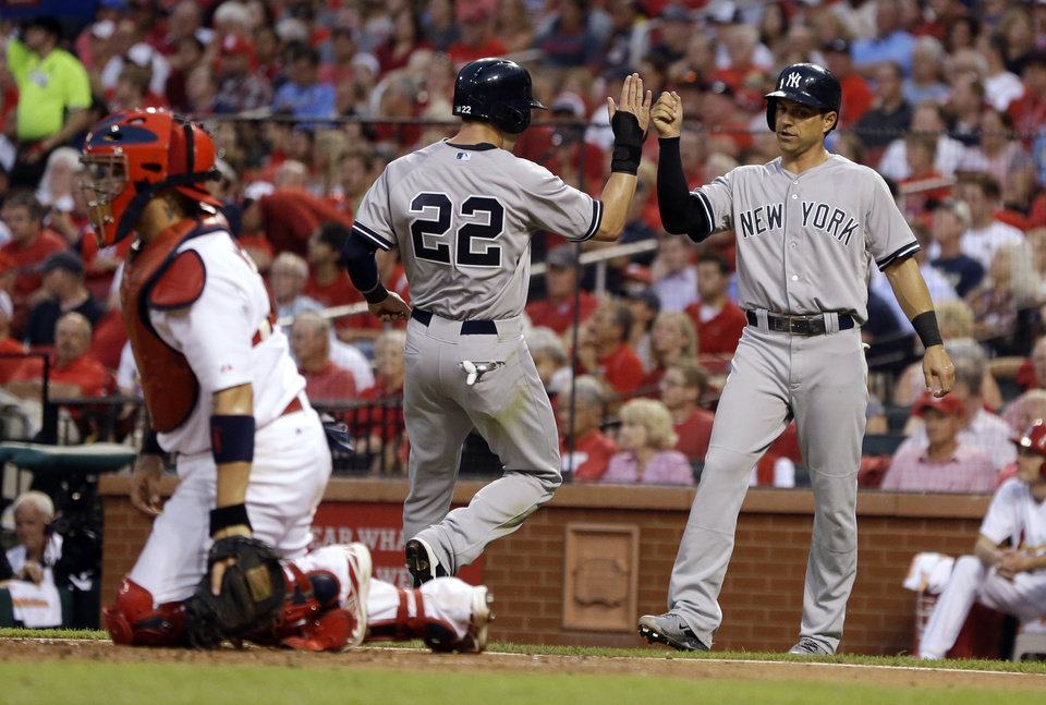 Photo - New York Yankees' Jacoby Ellsbury (22) and Brian Roberts, right, celebrate after scoring on a single by John Ryan Murphy as St. Louis Cardinals catcher Yadier Molina kneels at the plate during the third inning of a baseball game Wednesday, May 28, 2014, in St. Louis. (AP Photo/Jeff Roberson)
