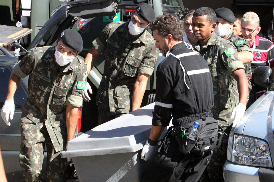 Photo - Brazil's soldiers carry a container with the remains of a victim outside a gymnasium where bodies were brought for identification in Santa Maria city, Rio Grande do Sul state, Brazil, Sunday, Jan. 27, 2013. Flames raced through a crowded nightclub in southern Brazil early Sunday, killing more than 230 people as panicked partygoers gasped for breath in the smoke-filled air, stampeding toward a single exit partially blocked by those already dead. (AP Photo/Nabor Goulart)