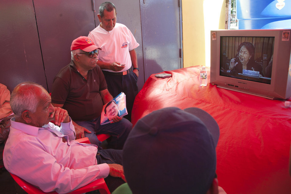 Photo - Supporters of Venezuela's President Hugo Chavez gather around a TV to watch Venezuela's Supreme Court President Luisa Estella Morales give a news conference, as they sit in Plaza Bolivar, a popular gathering place for Chavez supporters in Caracas, Venezuela, Wednesday, Jan. 9, 2013. Morales said that the upcoming inauguration of ailing Chavez can legally be postponed, amid a heated debate between the government and opposition over whether the constitution requires the cancer-stricken leader to be sworn in for a new term on Thursday. (AP Photo/Ariana Cubillos)