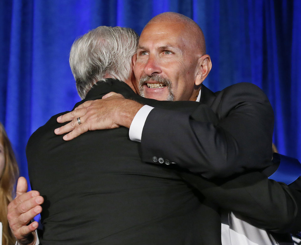Photo - Jon Hazell, right, a science teacher at Durant High School, is congratulated after being has named Oklahoma's Teacher of the Year for 2017, during a ceremony in Oklahoma City, Tuesday, Aug. 30, 2016. Hazell was named Oklahoma Teacher of the Year after extensive interviews with 12 finalists by a 28-member panel. (AP Photo/Sue Ogrocki)