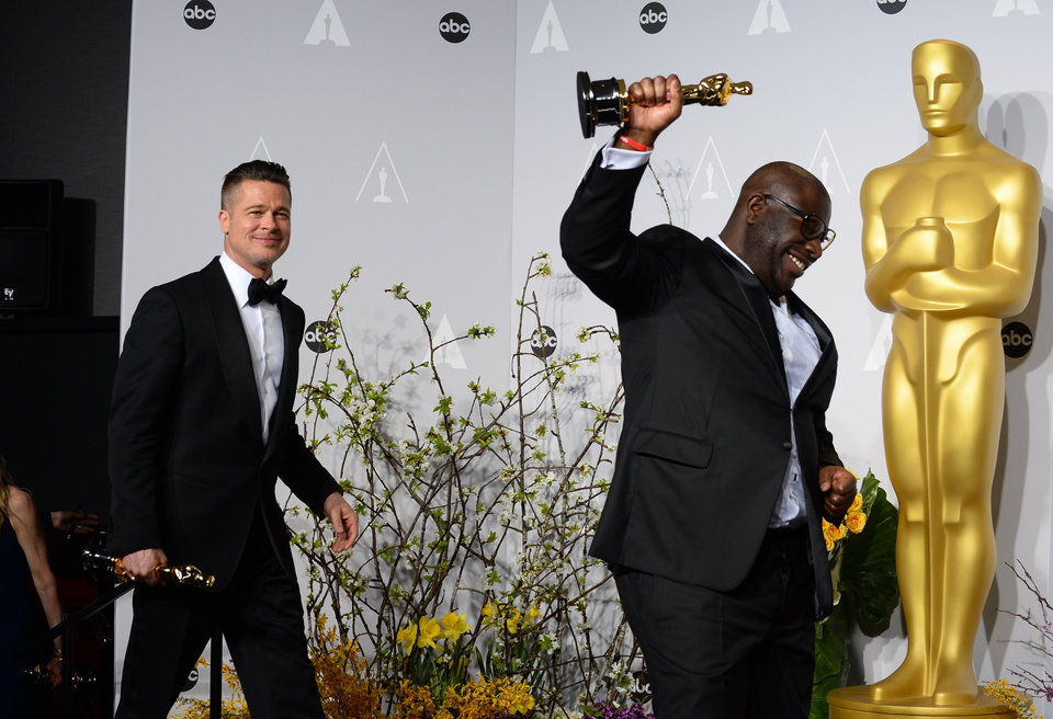 Photo - Brad Pitt, left, and Steve McQueen pose in the press room with the award for best picture for