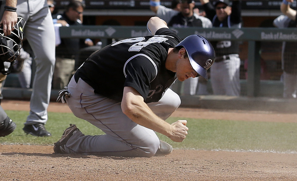 Photo - Colorado Rockies' DJ LeMahieu celebrates after scoring on Justin Morneau's two-run double off of San Francisco Giants pitcher Javier Lopez during the eighth inning of a baseball game in San Francisco, Sunday, June 15, 2014. (AP Photo/Jeff Chiu)