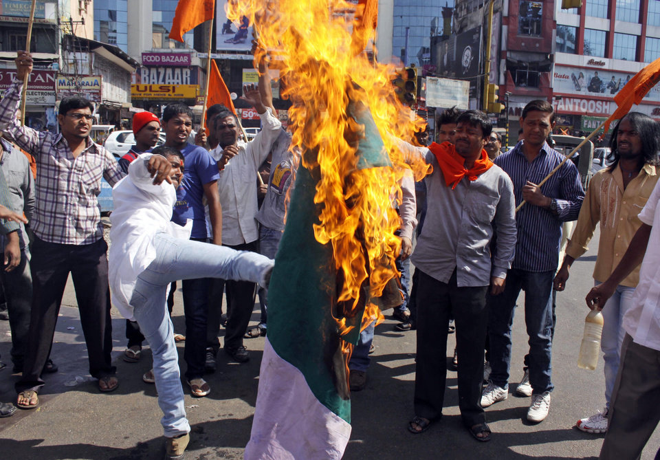 Photo - Activists of hindu nationalist Vishwa Hindu Parishad (or World Hindu Council) burn a flag of Pakistan during a protest in Hyderabad, India, Friday, Jan. 11, 2013. India has formally complained about an attack on an Indian army patrol in the disputed Himalayan region of Kashmir that killed two soldiers and left their bodies mutilated. India says Pakistani troops crossed the cease-fire line Tuesday and attacked Indian soldiers patrolling in the Mendhar region before retreating. (AP Photo/Mahesh Kumar  A.)