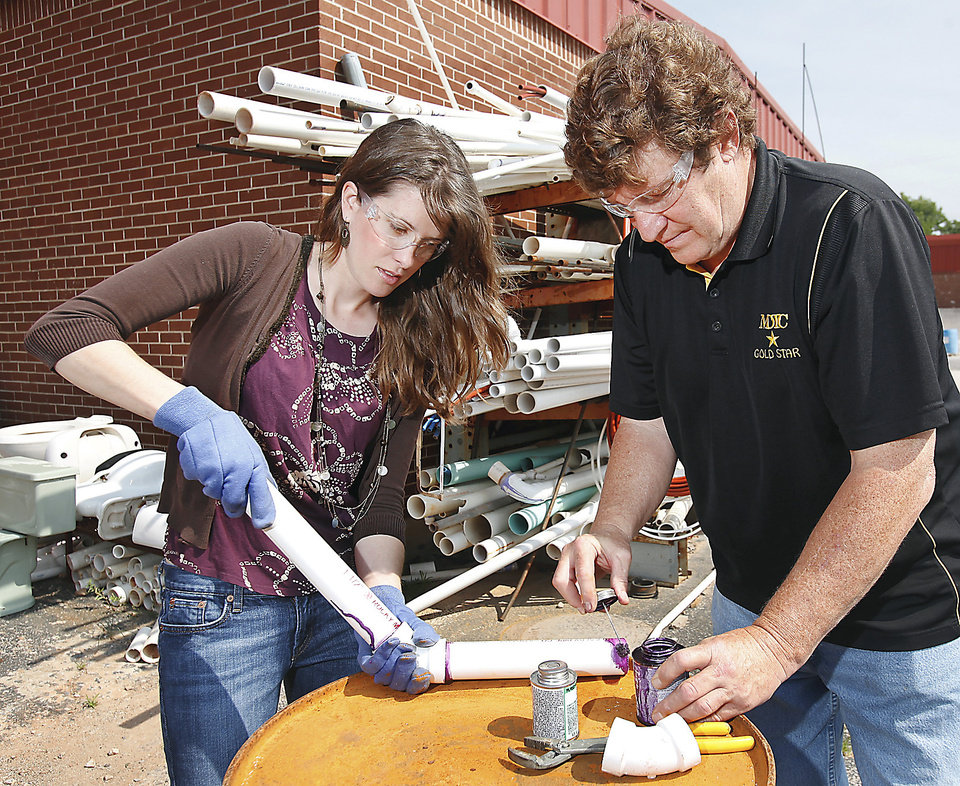 Photo - Tara Ward, a counselor at Monroney Middle School, learns pipe assembly using a solvent weld and PVC pipe. Showing her the proper method is Mid-Del Technology Center plumbing instructor Greg Dilbeck.  PHOTO BY JIM BECKEL, THE OKLAHOMAN