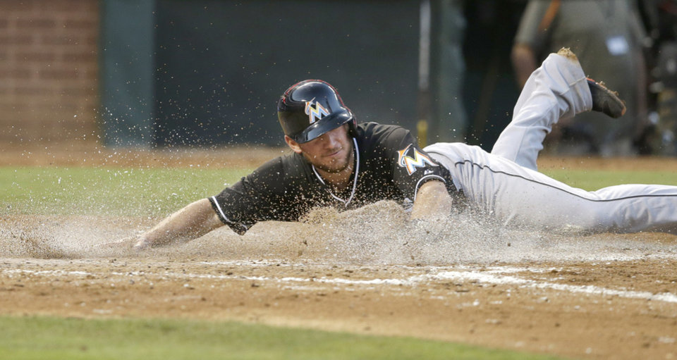 Photo - Miami Marlins Jeff Mathis slides into home plate scoring on a double by teammate  Christian Yelich during the fourth inning of a baseball game against the Texas Rangers in Arlington, Texas, Tuesday, June 10, 2014. (AP Photo/LM Otero)