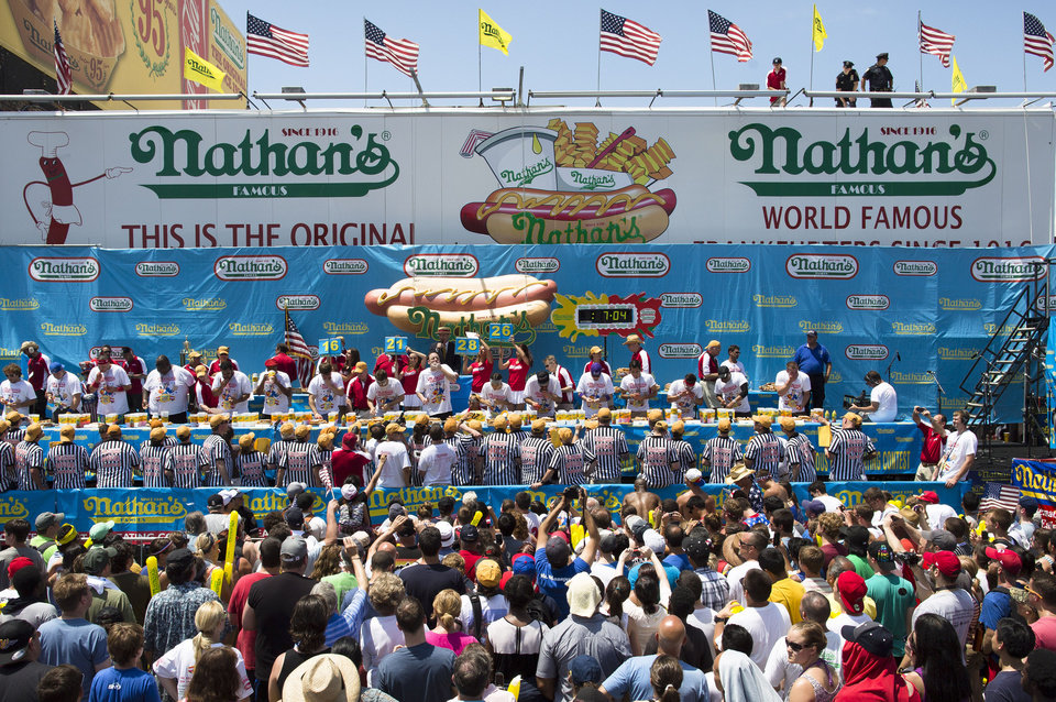 Photo - The Nathan's Famous Fourth of July International Hot Dog Eating contest men's competition kicks off in front of crowds of fans at Coney Island, Thursday, July 4, 2013 at Coney Island, in the Brooklyn borough of New York. (AP Photo/John Minchillo)