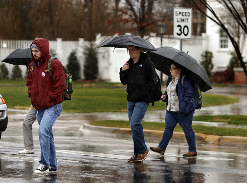 Photo - Umbrellas come out as students head to class in the rain on the campus of the University of Oklahoma (OU) on Tuesday, Feb. 12, 2013 in Norman, Okla.  Photo by Steve Sisney, The Oklahoman