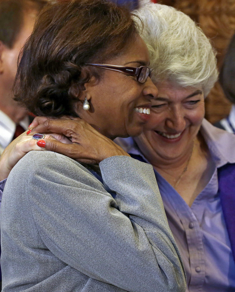 Photo - Rep. Rhonda Fields, left, D-Aurora, and Rep. Lois Court, D-Denver, embrace after Colorado Gov. John Hickenlooper signed gun control bills into law at the Capitol in Denver on Wednesday, March 20, 2013. (AP Photo/Ed Andrieski, Pool)