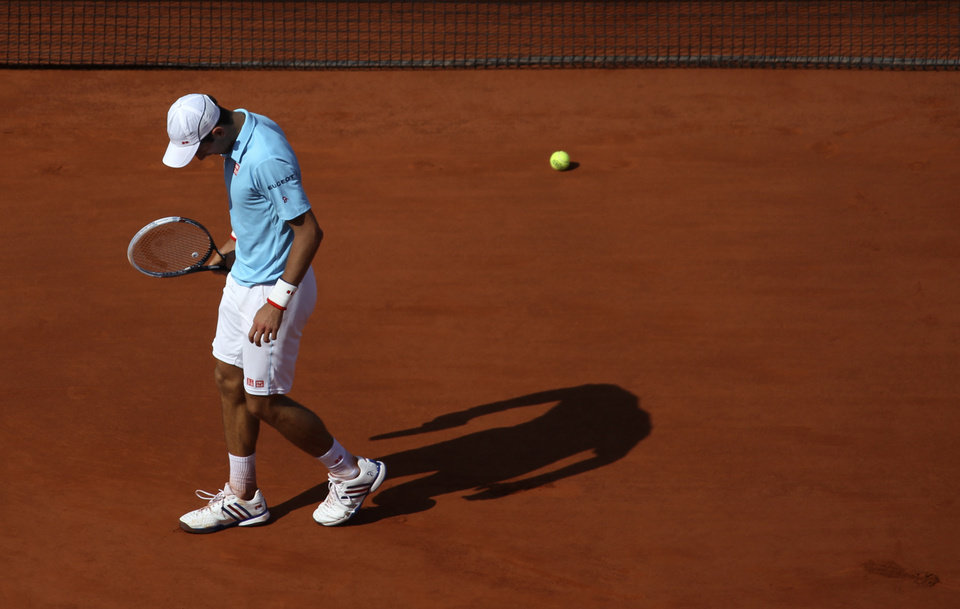 Photo - Serbia's Novak Djokovic bows his head as he plays Spain's Rafael Nadal during their final match of  the French Open tennis tournament at the Roland Garros stadium, in Paris, France, Sunday, June 8, 2014. (AP Photo/David Vincent)