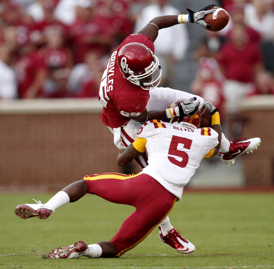 Photo - OU's Ryan Broyles leaps over Iowa State's Jeremy Reeves during the first half of the college football game between the University of Oklahoma Sooners (OU) and the Iowa State Cyclones (ISU) at the Glaylord Family-Oklahoma Memorial Stadium on Saturday, Oct. 16, 2010, in Norman, Okla.   Photo by Bryan Terry, The Oklahoman